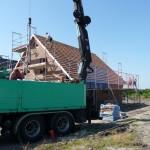 Ein Kran liefert die Dachpfannen direkt aufs Dach