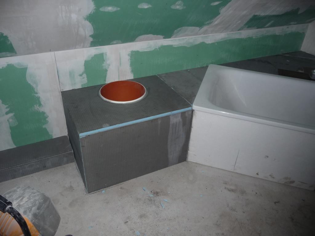 """Hier hat der Fliesenleger die """"Abmauerung"""" neben der Badewanne so verlängert, dass das Wäscherohr mit eingefasst ist"""