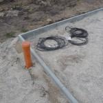 Kabel liegen im Inneren der Auffahrt und der Abfluss außerhalb